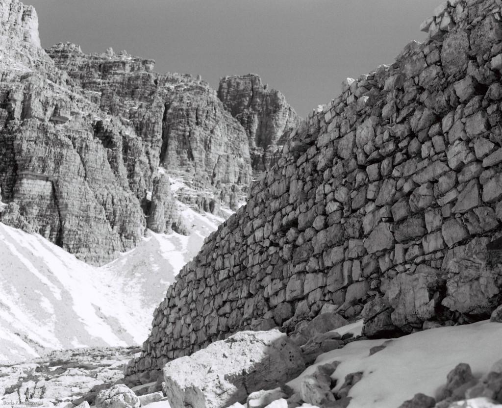Blick auf eine Felswand gegenüber den Drei Zinnen (Dolomiten), im Vordergrund eine Mauer aus Bruchsteinen